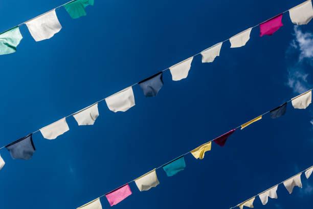 bunte girlanden vor blauem himmel - horizontal gestreiften vorhängen stock-fotos und bilder
