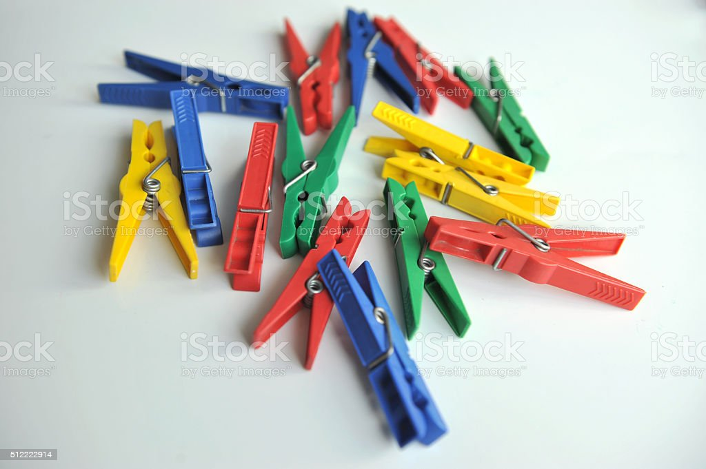 Multi-coloured clothespins on the white background stock photo