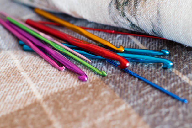 multicolores au crochet crochets sur une couverture de tartan bleu et beige - icône de ligne photos et images de collection