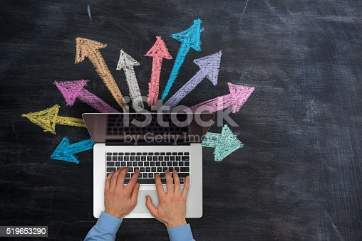 Businessman  typing on laptop on top of black grunge background. Multicoloured hand drawn arrows are going out of the laptop.