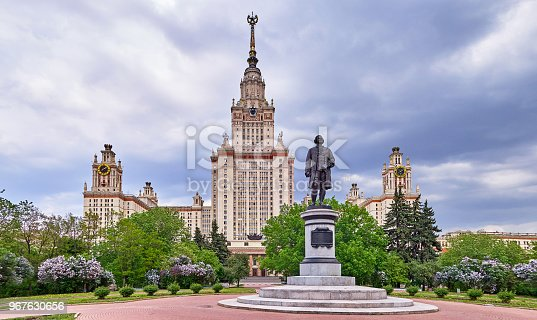 A highly vibrant soft image of multicoloured lilac trees in spring in the campus of Moscow university under dramatic sky and a statue of MSU founder Mikhailo Lomonosov.