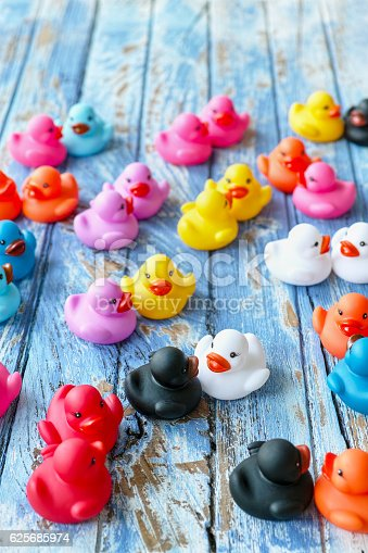 istock Multi-coloured rubber duck couples on an old wooden background. 625685974