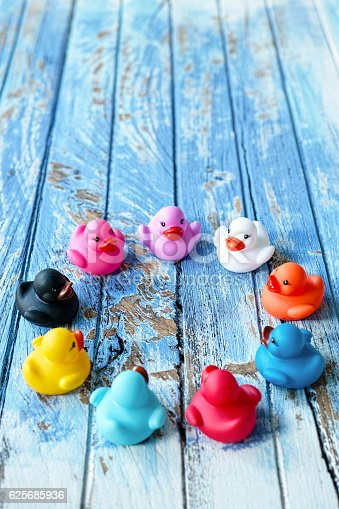 istock Multi-coloured rubber ducks facing each other in a circle. 625685936