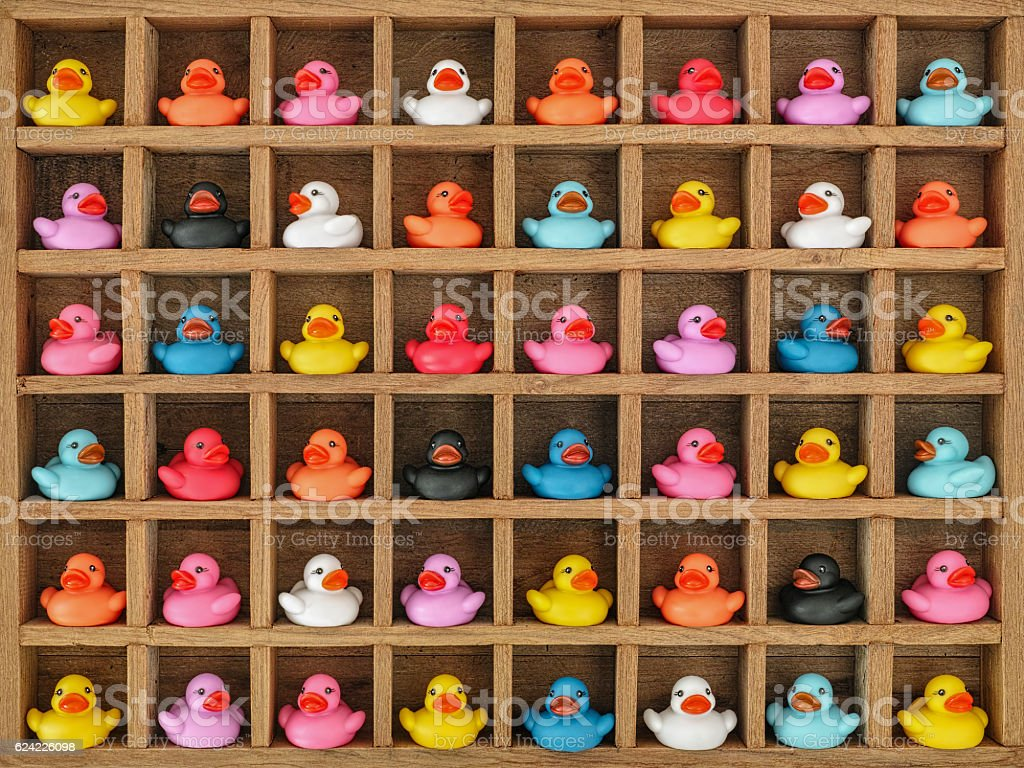 Multi-coloured rubber ducks in pigeon hole boxes. stock photo