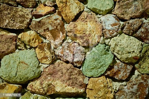 istock Multi-coloured stones forming a wall. Soft natural colours of the stones. 1169676925