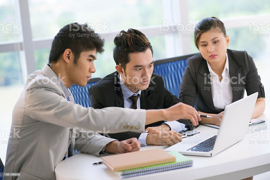 Multicultural business associates conversing around a laptop royalty-free stock photo