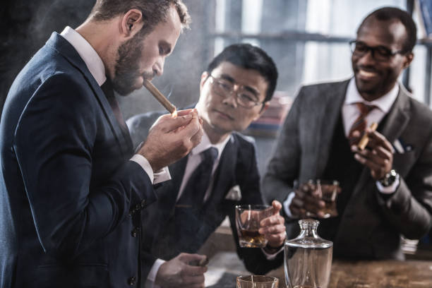 multiculturele business team tijd doorbrengen, sigaren roken en drinken van whisky - guy with cigar stockfoto's en -beelden