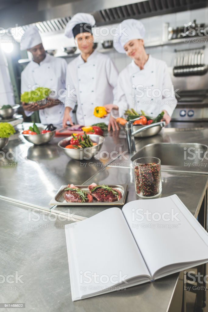 Multicultural Chefs At Restaurant Kitchen With Recipe Book On