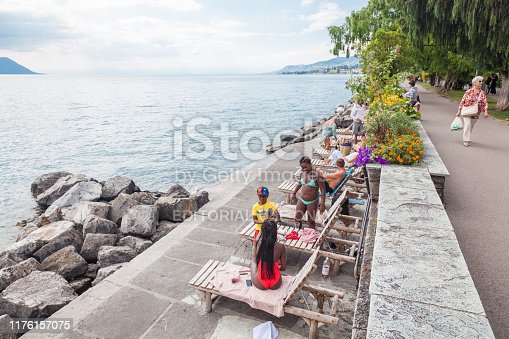 Multicultural community enjoying summer weather on beach along Geneva lakeside and Montreux Riviera promenade in Montreux, Vaud, Switzerland
