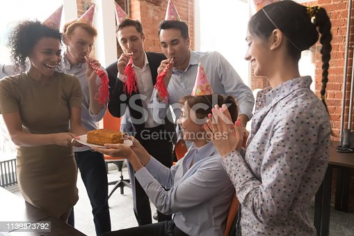 istock Multicultural employees in party hats congratulate female with birthday cake 1139873792