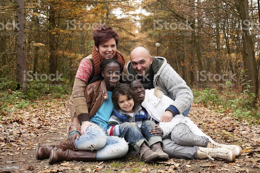 Multicultural family posing in the woods during autumn stock photo