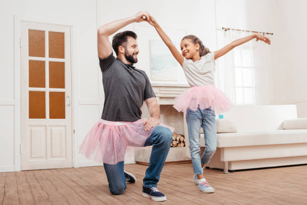 multicultural father and daughter in pink tutu tulle skirts dancing at home - father and daughter stock photos and pictures