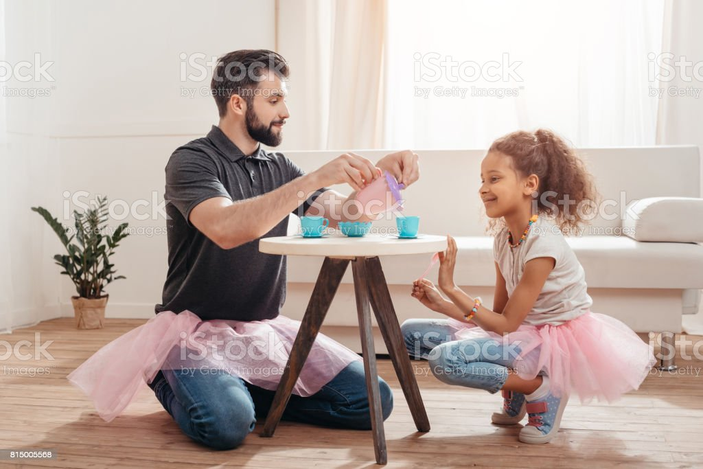 multicultural father and little daughter having tea party at home stock photo