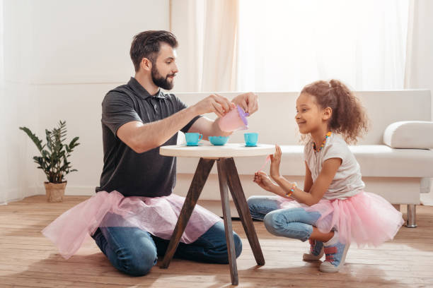 multicultural father and little daughter having tea party at home - father and daughter stock photos and pictures