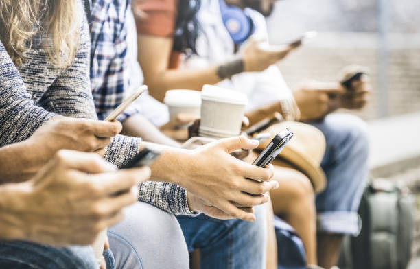 Multicultural friends group using smartphone with coffee at university college break - People hands addicted by mobile smart phone - Technology concept with connected trendy millennials - Filter image stock photo