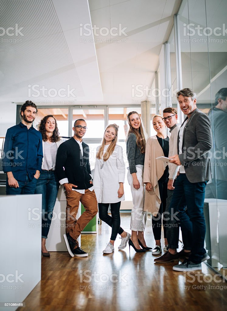 Multi-cultural group employees standing together during a office studio meeting. stock photo