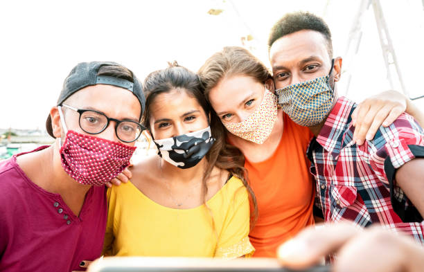 Multicultural milenial travelers taking selfie with closed face masks - New normal travel concept with young people having safe fun together at ferris wheel - Bright warm sunshine filter stock photo