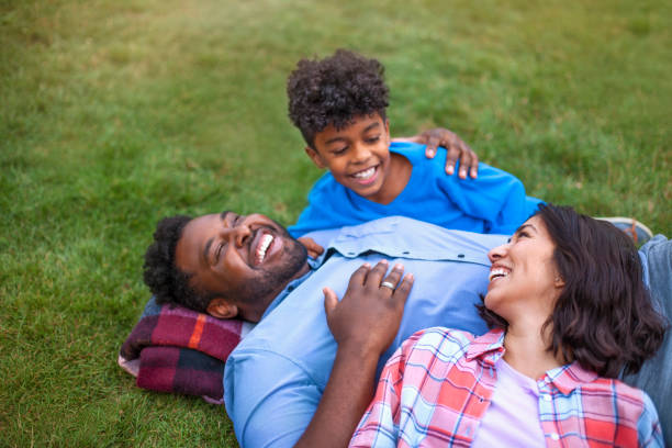 Multicultural mixed race multi-ethnic family with one child laying on grass laughing stock photo