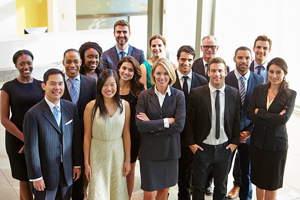 Multi-cultural office staff standing in lobby stock photo