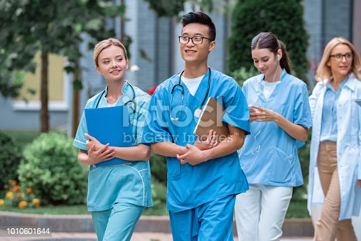 multicultural students and teacher walking on street near medical university