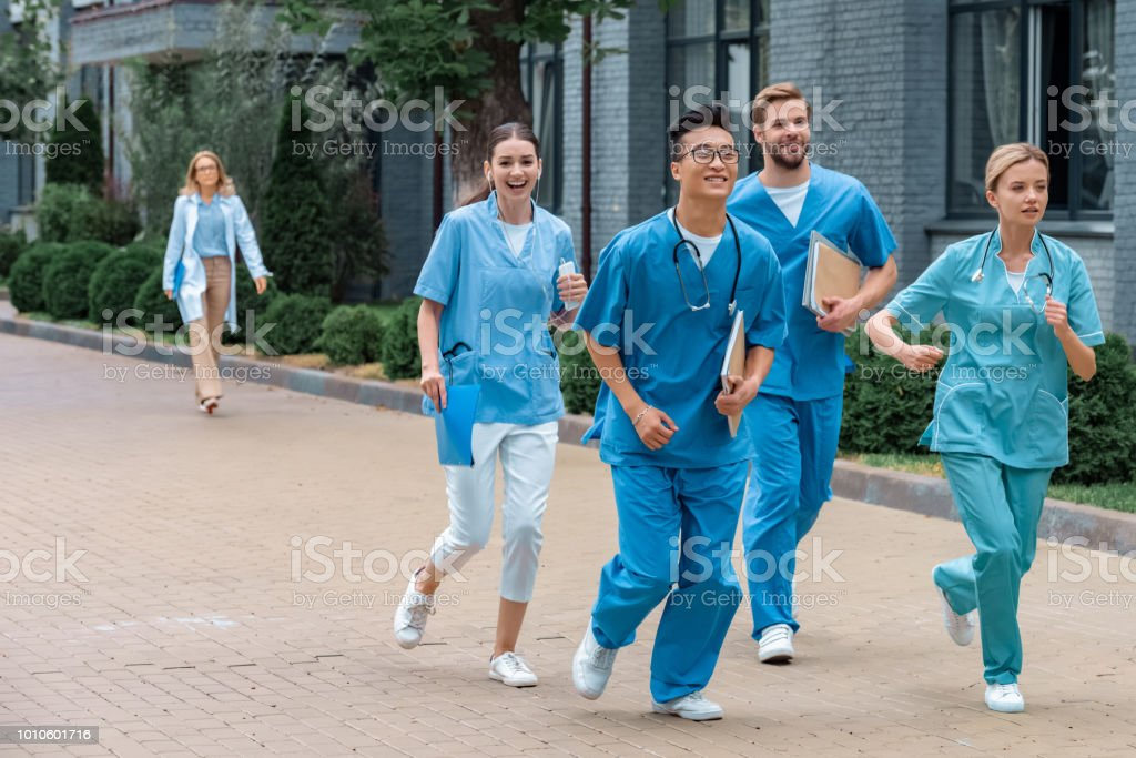 multicultural students running near medical university stock photo