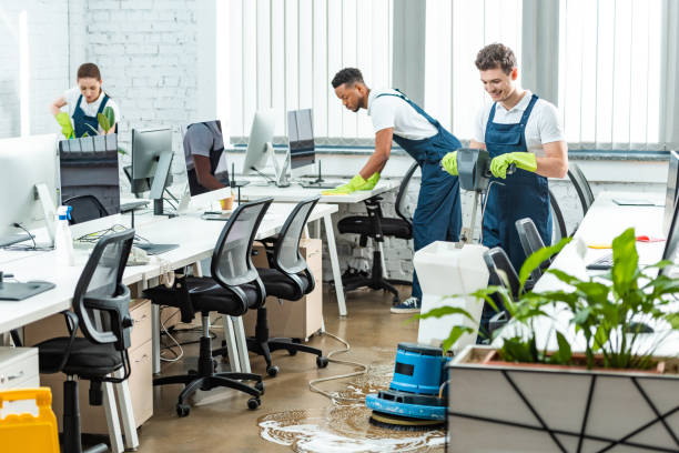 multicultural team of cleaners working in modern open space office stock photo