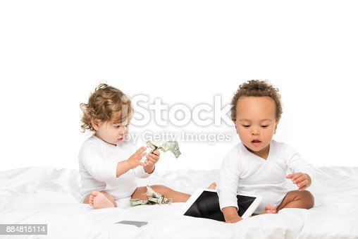 istock multicultural toddlers with cash and tablet 884815114