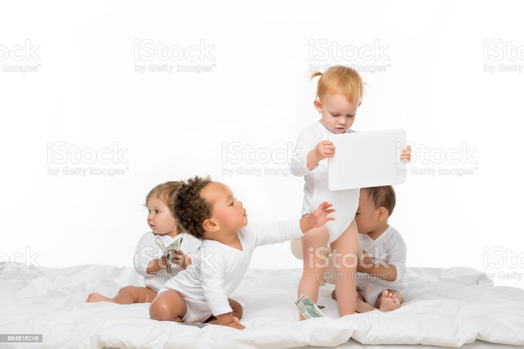 multicultural toddlers with money and tablet stock photo