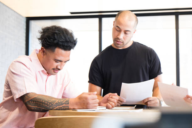 Multicultural workplace - Samoan and Maori/mixed ethnicity co-workers reviewing report documents in a business meeting stock photo