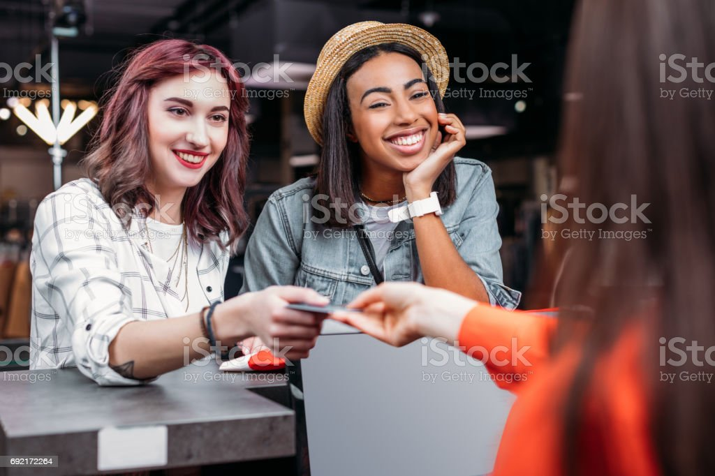 multicultural young girls shopping and paying with credit card in boutique, fashion shopping girls concept stock photo