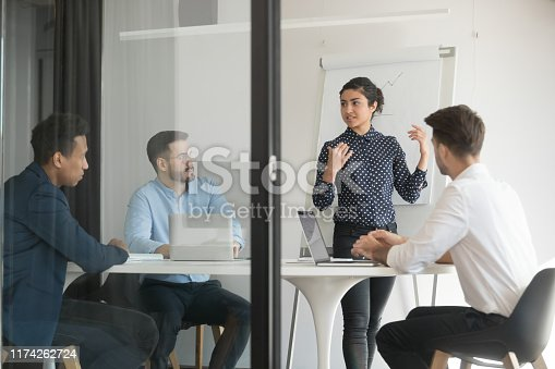 Board room view through glass door diverse businessmen listens hindu firm representative give presentation make offer to investors. Staff takes part in seminar, corporate trainer teach workers concept