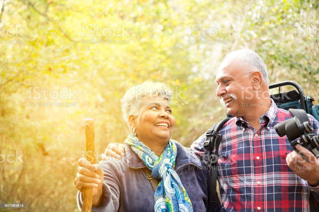Multi-étnico, ativo casal adulto sênior caminhadas na arborizada área de floresta. - foto de acervo