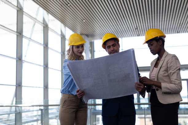 Multi-ethnic architects discussing over blueprint in office stock photo