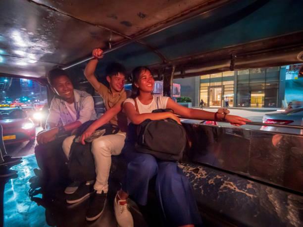 夜マニラでジープニーに乗っている多民族アジアの友人 - jeepney ストックフォトと画像