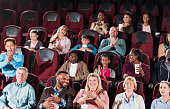 Multi-ethnic audience in movie theater, clapping