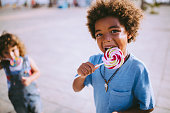 Multi-ethnic children friends with curly hair and colourful lollipops outdoors on summer vacations