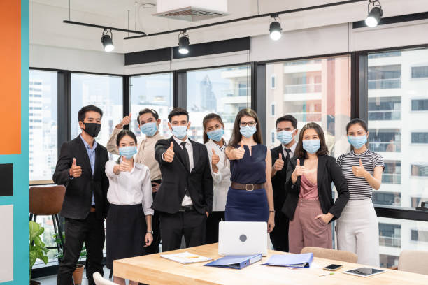 Multi-ethnic business group confident wearing face mask and showing thumbs up in new normal office at business district stock photo