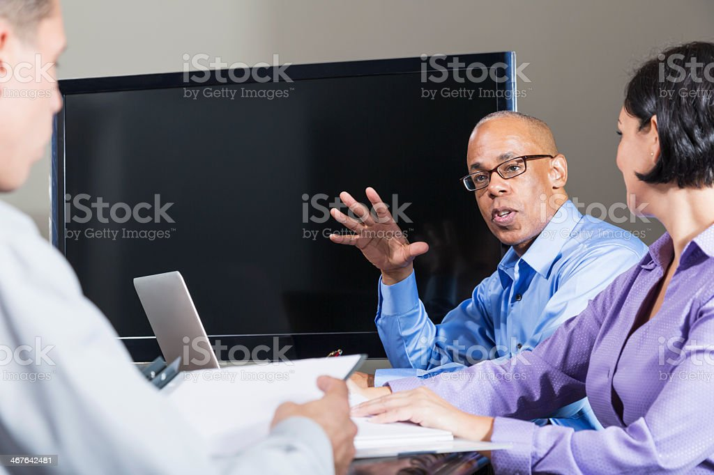 Multi-ethnic business meeting, African American businessman talking stock photo