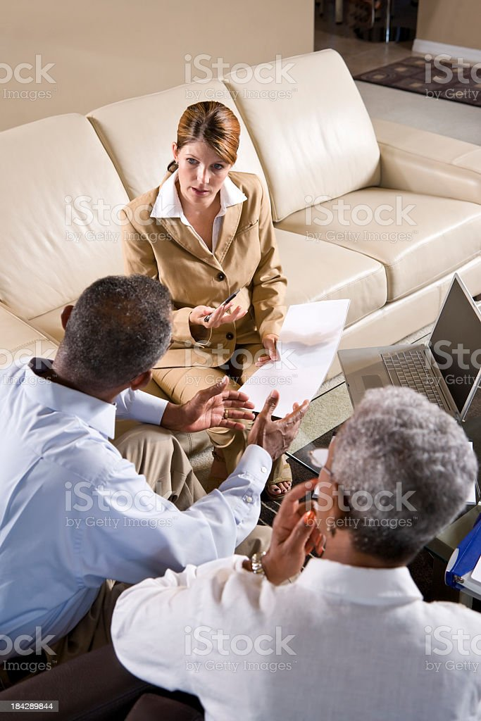 Multi-ethnic business meeting discussing papers on couch stock photo