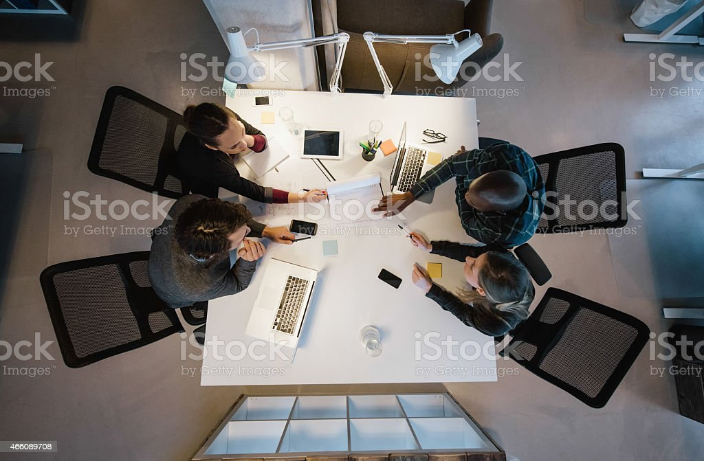 Office workers gather around a table to do research and implement new...