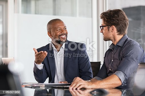 Two happy business colleagues at meeting in modern office interior. Successful african boss in a conversation with young employee in boardroom. Marketing team of two businessmen discussing strategy in meeting room.