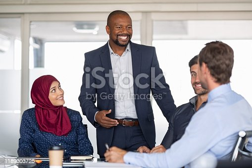 Entrepreneurs, partners and islamic woman conference in modern meeting room. Happy mature african businessman putting forward his suggestions to colleagues. Group of multiethnic business people brainstorming together.