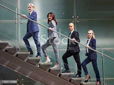 84743203 istock photo multiethnic business people walking on stairs 1020742050