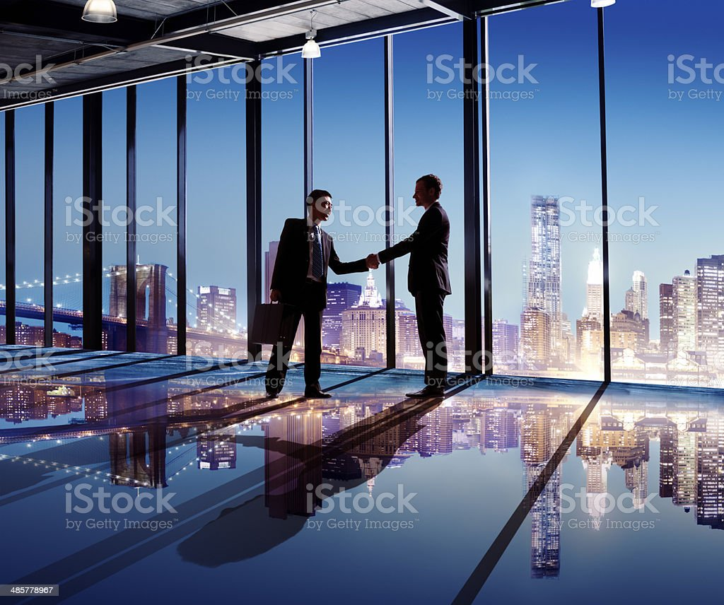 Multi-Ethnic Businessmen Shaking Hands Indoors With City As A Background Multi-Ethnic Businessmen Shaking Hands Indoors With City As A Background Adult Stock Photo