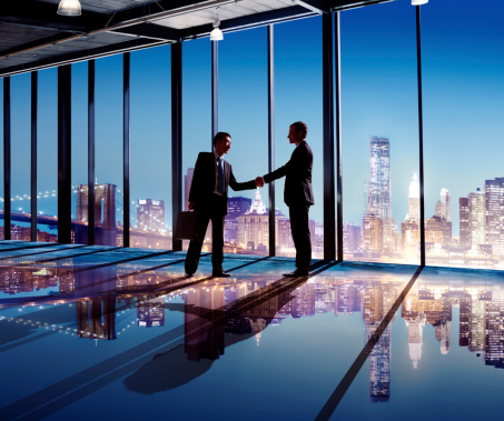 Multiethnic Businessmen Shaking Hands Indoors With City As A Background Stock Photo - Download Image Now