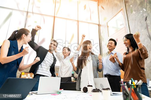 932724052 istock photo Multi-ethnic businesspeople cheering with business project successful in meeting room office backgroound 1214655227