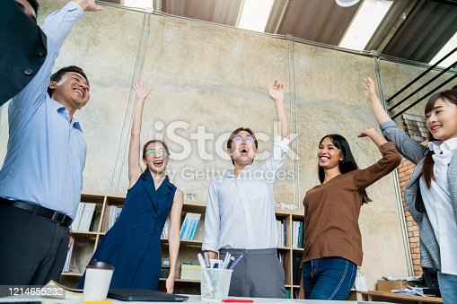 1016196912 istock photo Multi-ethnic businesspeople cheering with business project successful in meeting room office backgroound 1214655232