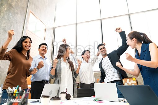 932724052 istock photo Multi-ethnic businesspeople cheering with business project successful in meeting room office backgroound 1214655802