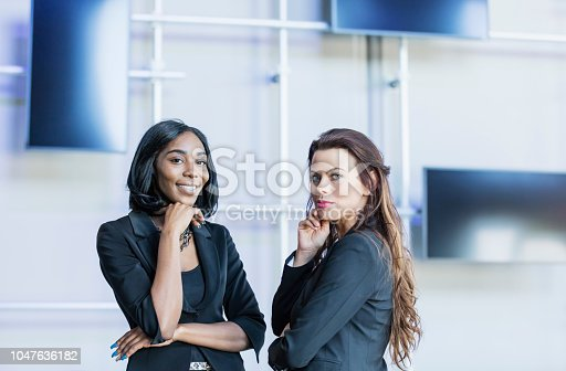 Two multi-ethnic businesswomen standing, looking at the camera. The young African-American woman, in her 20s, is smiling. Her coworker, 30 something years old, has a serious expression.