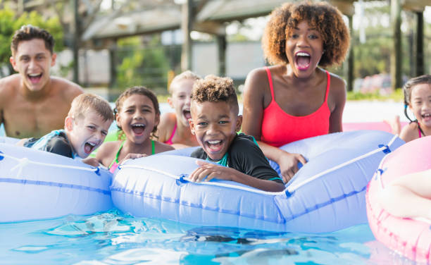 Multi-ethnic children and young adults at water park stock photo